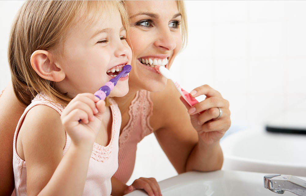 Child brushing her teeth with her mother